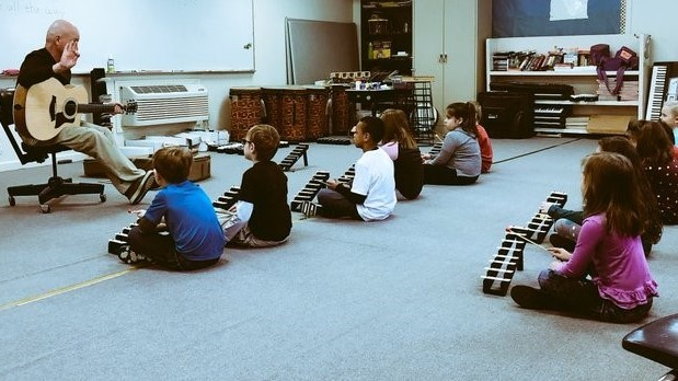 Mr. Brock teaches first grade students to use percussion.